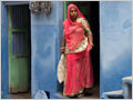 Woman leaving her home and going to market in the old part of Udaipur, Rajasthan, India.