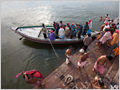 A group of people embarking the boat on one of the many Ganges ghats where people take baths in holy river, Varanasi, Uttar Pradesh, India.