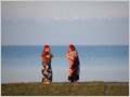Two woman washing on the bank of lake Issyk Kul, Kyrgyzstan.