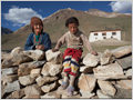 A young girl and her grandmother in front of a traditional Ladakhi house, Rangdum, Ladakh, Jammu and Kashmir, India.