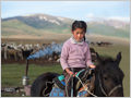 A young nomad shepherdess riding a horse near her yourt camp at lake Song Kul, Kyrgyzstan.