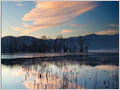 Pink cirrus clouds reflected in the calm waters of lake Cerknica, Slovenia.