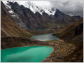 A break in the dramatic clouds above Mt. Siula Grande and the Laguna Quesillococha, Cordillera Huayhuash, Peru.