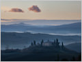 Two clouds hovering over the misty landscape of San Quirico D'Orcia, Tuscany, Italy.