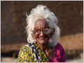 An old woman with white hair wearing ruined eyeglasses with one dirty lense, Varanasi, Uttar Pradesh, India.