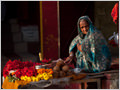 An old woman selling offering items near one of the Hindu temples in Varanassi, Uttar Pradesh, India.
