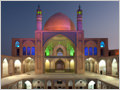 The symetrically designed Agha Bozorg mosque, lit up in colors, Kashan, Iran.