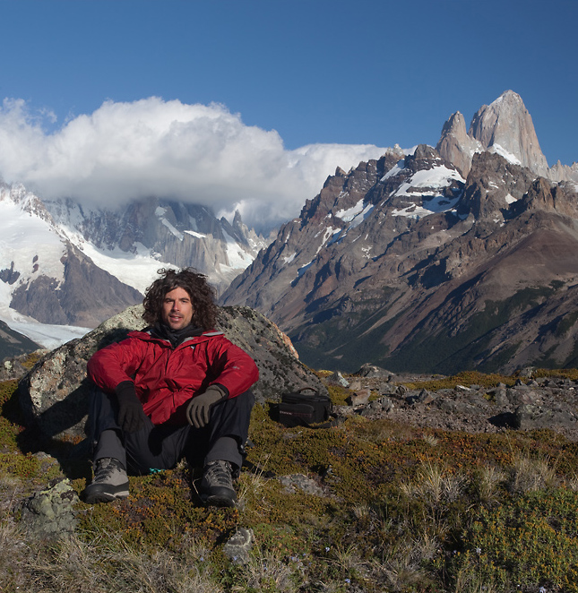 Jernej Trnkoczy resting on a trekking below Mt. Fitz Roy and Mt. Cerro Torre (in the clouds).