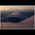 Sunrise among frozen sand dunes near the Farahzad village in the Dasht-e Kavir desert, Iran.